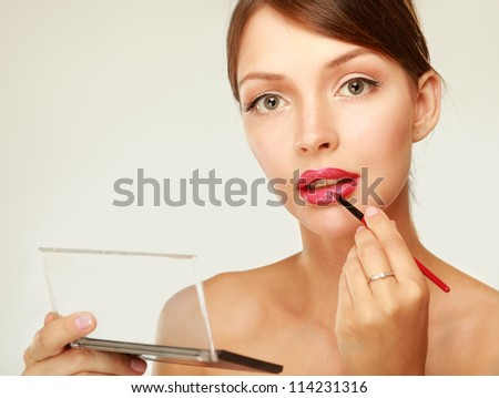 A beautiful young woman doing make-up, isolated on white - stock photo