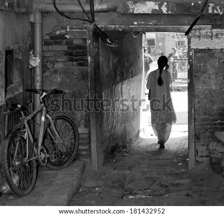 A beautiful young woman enters the yard - Kathmandu, Nepal (black and white) - stock photo