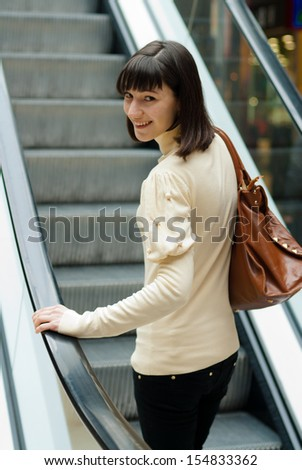 A beautiful young woman happy smiling & looking at camera on escalator at shopping center