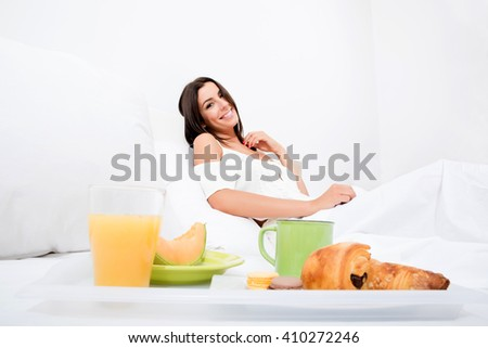 A beautiful young woman having breakfast in the early morning in bed.