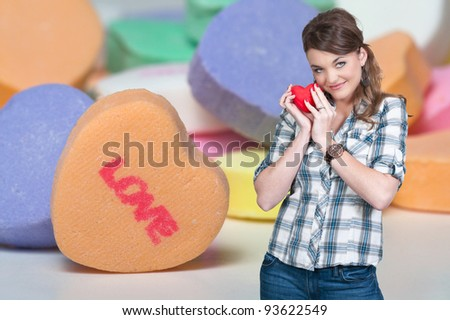 A beautiful young woman holding a Valentines Day heart and candy - stock photo