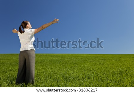 A beautiful young woman holding her arms out in praise or celebration standing in a green field and facing towards the light in a blue sky