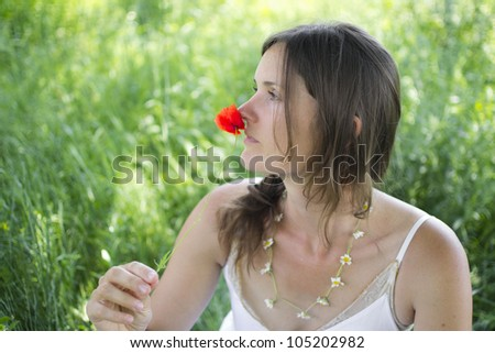 A beautiful young woman holds a poppy to her nose, sitting in a meadow