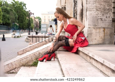 A beautiful young woman in a vintage dress in a european city.