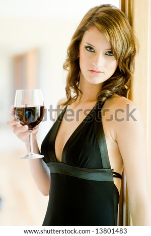 A beautiful young woman in black dress holding glass of red wine