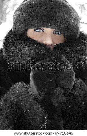 A beautiful young woman in faux fur coat and hat outdoors in winter on a light snowy day. - stock photo