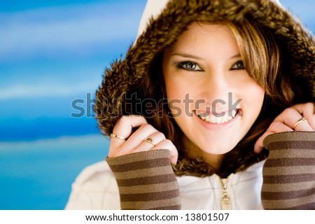 A beautiful young woman in fur-lined coat on blue background