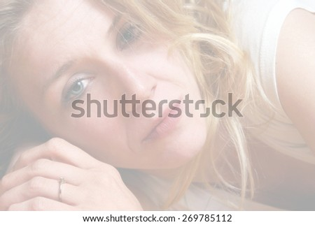 A beautiful young woman in her twenties is pictured in a fashionable pose of a dreamy stare. - stock photo