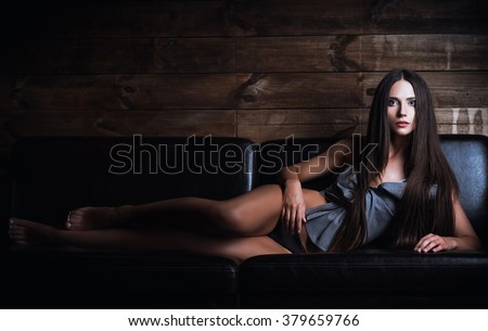 A beautiful young woman in panties and shirt lying on sofa  - stock photo