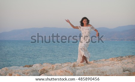 A beautiful young woman in the dress dancing on the rocks and smiling. A charming lady enjoying the view to the sea. Sunset in Cyprus. Island life. Romantic mood