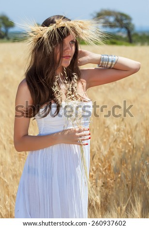 A beautiful young woman is in the field with a wreath - stock photo