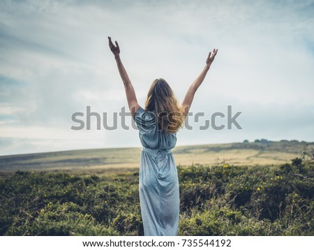 A beautiful young woman is wearing an elegant dress and is raising her arms on the moor