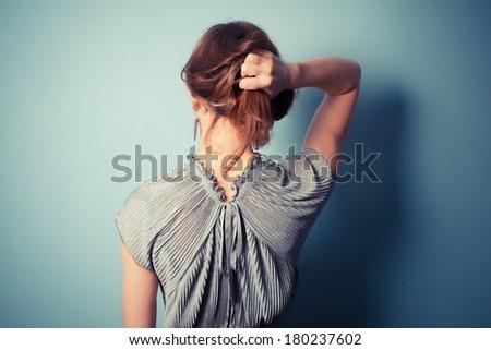 A beautiful young woman is wearing an elegant evening dress - stock photo