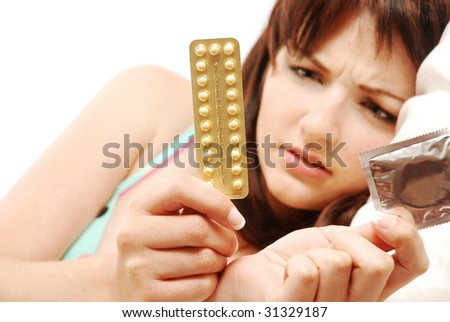A beautiful young woman lying in bed confused about contraception. She is looking at contraceptive pills and condoms and can't decide. - stock photo