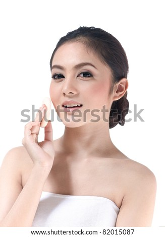 A beautiful young woman making up her face - stock photo