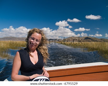 A beautiful young woman on a boat at lake Titicaca, Peru - stock photo