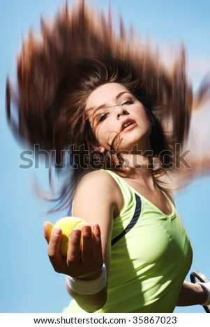 A beautiful young woman paying tennis in motion, holding the ball about to serve. - stock photo