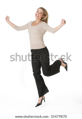 A beautiful young woman posing with her leg in the air.  She is smiling at the camera.  Vertically framed shot.