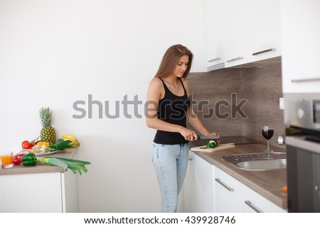A beautiful young woman preparing a healthy meal. Fresh vegetables and fruits. Modern interior, new kitchen.