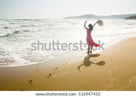 A beautiful young woman raises her arms towards the sea - stock photo