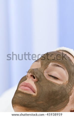 A beautiful young woman relaxing and having a chocolate face mask facial at a health spa - stock photo