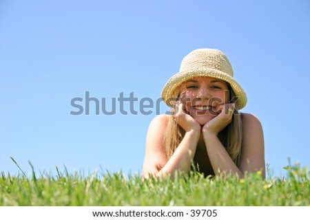A beautiful young woman relaxing in the grass.