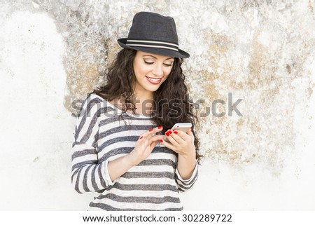 A beautiful young woman sending a text message - stock photo