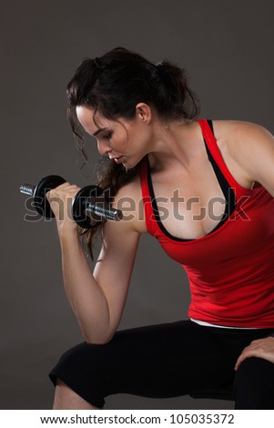 A beautiful young woman sitting down lifting weights - stock photo