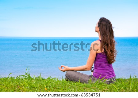 A beautiful young woman sitting meditating with a view of a lovely blue ocean