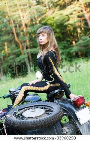 A beautiful young woman sitting on a black motorbike.