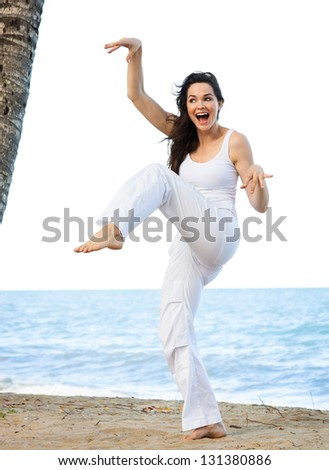 A beautiful young woman smiling as she is doing a silly and funny yoga pose on a beach. - stock photo