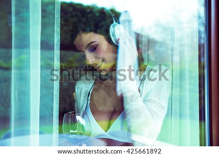 A beautiful young woman standing in the window in underwear enjoying a glass of wine and listening music on a headphone. - stock photo