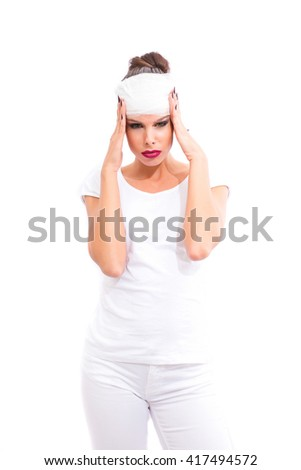 A beautiful young woman standing with bandage on her head. - stock photo