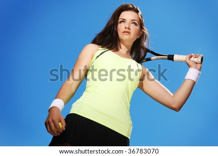 A beautiful young woman standing with her tennis racket and ball in front of a blue sky.