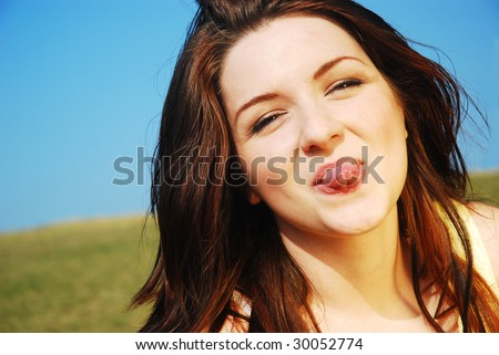 A beautiful young woman sticking her tongue out on a field with a blue sky. - stock photo