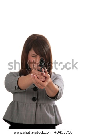 a beautiful young woman takes aim with a hand gun, isolated on white - stock photo