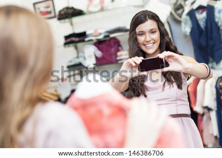 A beautiful young woman taking a photo of her friend at a boutique. - stock photo