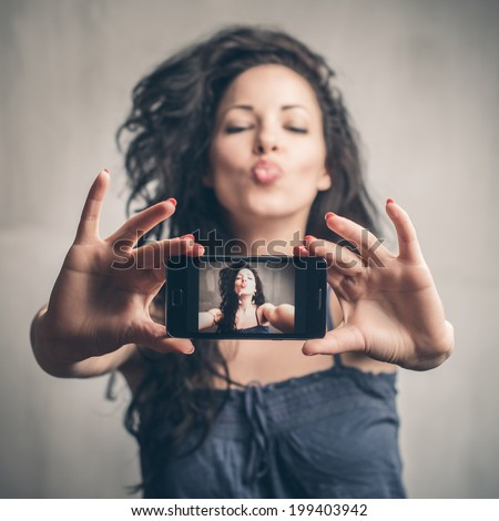 A beautiful young woman taking a picture of herself - stock photo