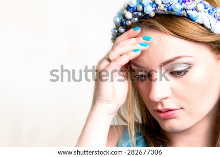 a beautiful young woman thinks and touches a hand a forehead - stock photo