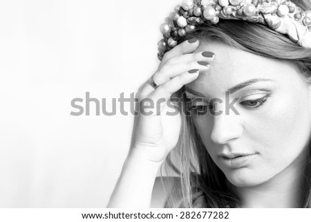a beautiful young woman thinks and touches a hand a forehead in bw - stock photo