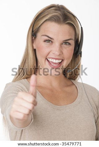 A beautiful young woman wearing a headset and making a 'thumbs up' gesture.  She is smiling excitedly and is looking directly at the camera. Vertically framed shot.