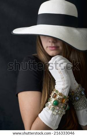 A beautiful young woman with a large floppy hat, long white gloves and lots of bling! - stock photo