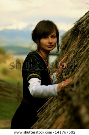A beautiful young woman with dark hair, black velvet historical dress and a subtle smile is touching gently the rough surface of an ancient straw house roof profile portrait eye contact make up artist - stock photo