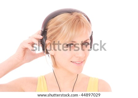 A beautiful young woman with headphones listening music - stock photo