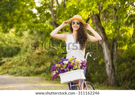 A beautiful young woman with her bicycle full of wildflowers  - stock photo