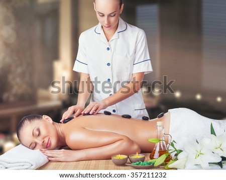 A beautiful young woman with her eyes closed getting a massage at the spa - stock photo