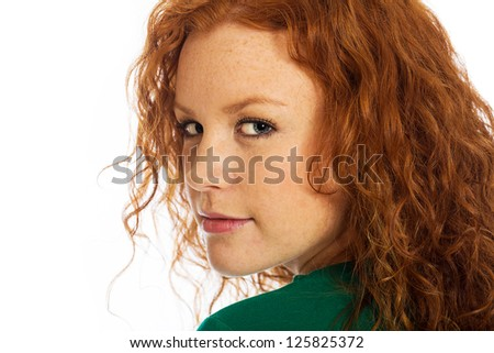A beautiful young woman with naturally curly red hair and cute freckles. - stock photo