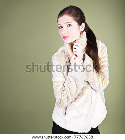 A beautiful young woman with pink lips in a fur coat - stock photo