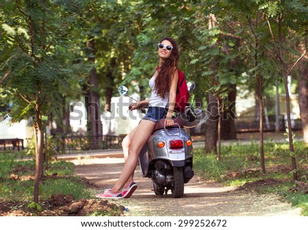 A beautiful young woman with sunglasses sitting on a scooter in a city street