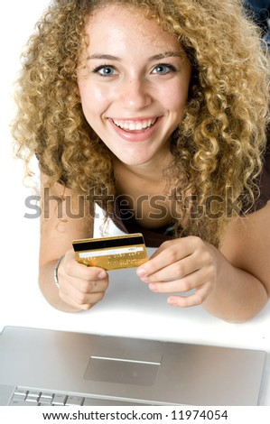 A beautiful young women using a credit card and a computer to shop online - stock photo